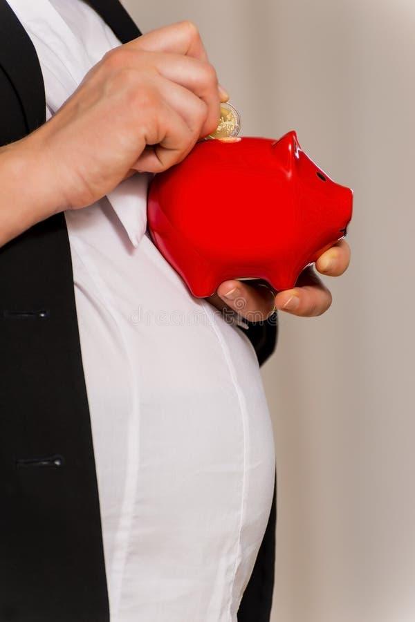 Schwangere Geschäftsfrau mit piggy Querneigung lizenzfreies stockfoto