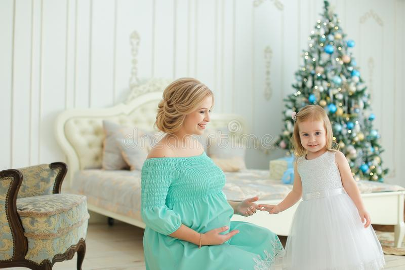 Schwangere glückliche Frau, die das blaue Kleid umarmt Bauch und sitzt mit kleiner Tochter nahe Weihnachtsbaum im Schlafzimmer tr stockfotos