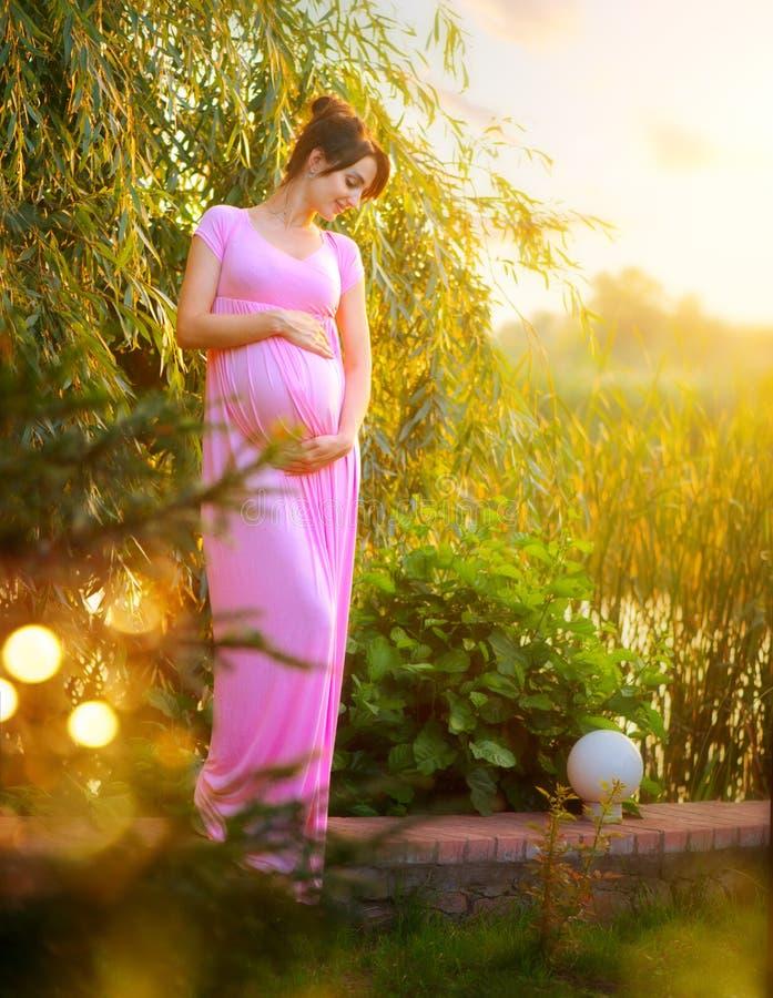 Schwangere glückliche Frau, die ihren Bauch im Sommerpark streichelt Der in voller Länge Porträt schwangeren Schönheitsfrau im Fr lizenzfreies stockbild