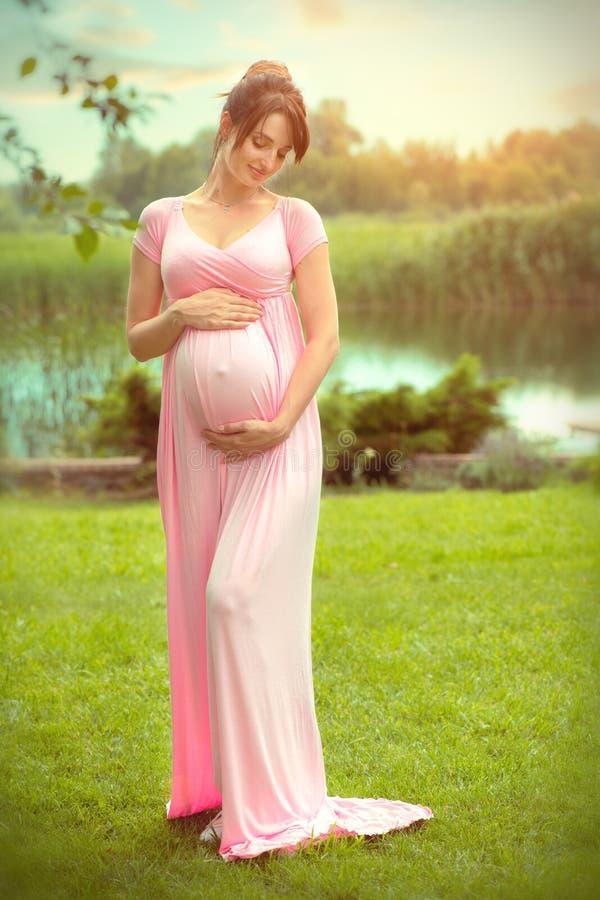 Schwangere glückliche Frau, die ihren Bauch im Sommerpark streichelt Der in voller Länge Porträt schwangeren Schönheitsfrau im Fr stockfotos