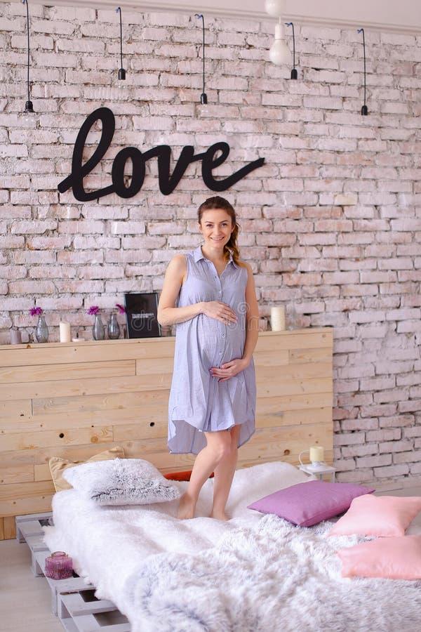 Schwangere hübsche Frau, die das blaue Kleid hält Bauch, Aufschriftliebe auf Backsteinmauer trägt stockfotos