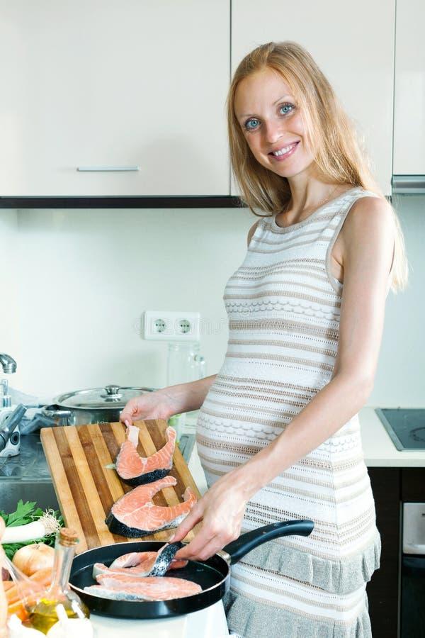 Schwangere Hausfrau, die Lachse kocht stockfoto