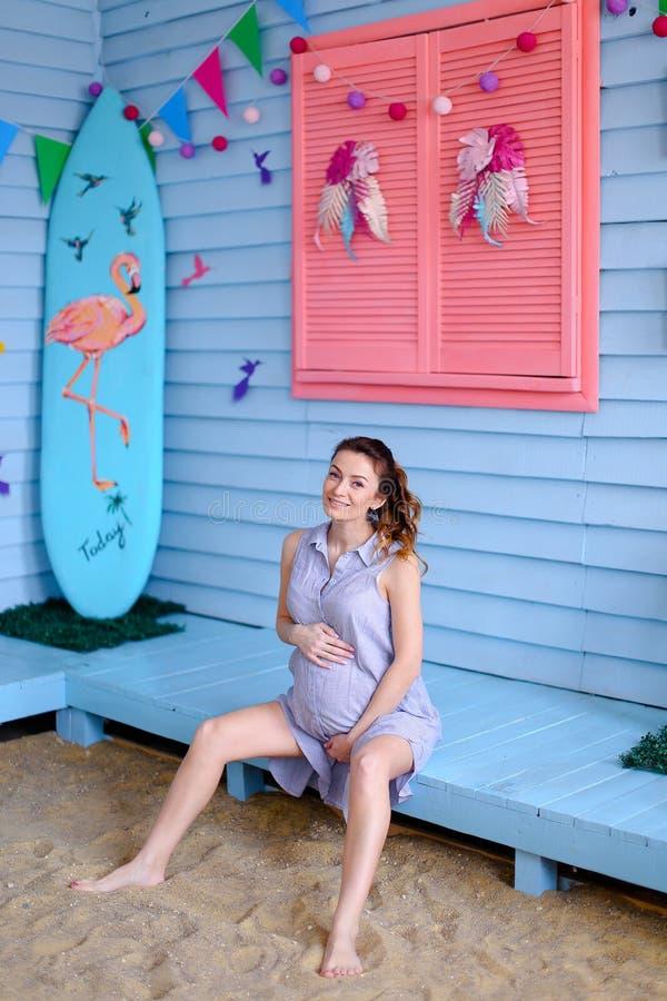 Schwangere junge Frau, die auf Bank nahe Kind-houe sitzt und Bauch hält lizenzfreie stockfotos