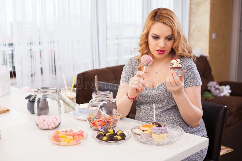 Schwangere junge Frau, die Bonbons isst lizenzfreie stockfotos