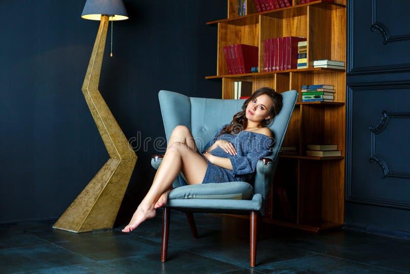 Schwangere junge Frau, die in einem Stuhl sitzt lizenzfreie stockfotos