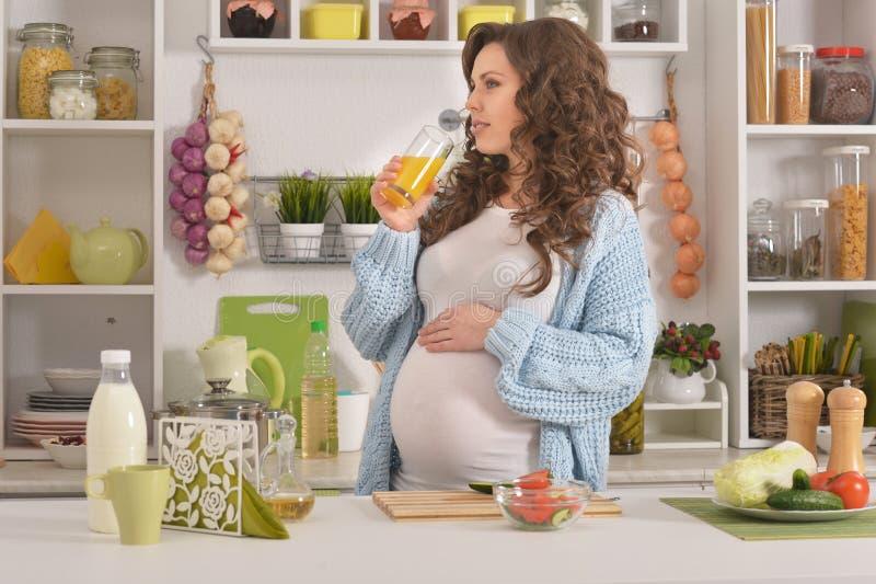 Schwangere junge Frau, die frühstückt lizenzfreie stockfotografie