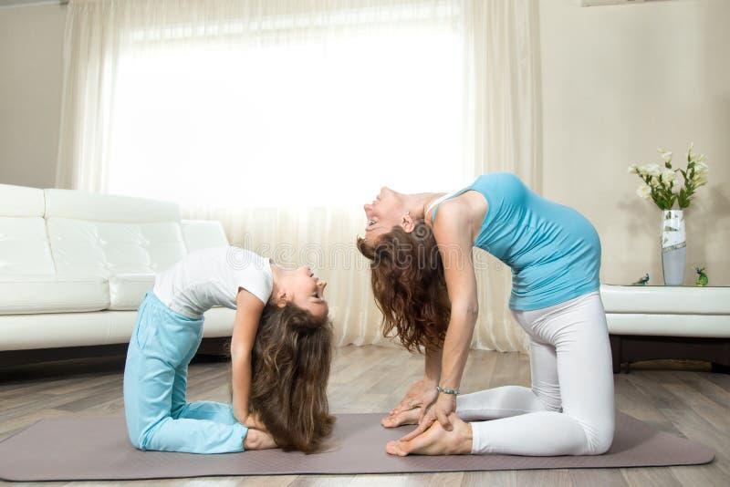 Schwangere junge Frau, die pränatales Yoga mit ihrem wenig daughte tut lizenzfreies stockfoto