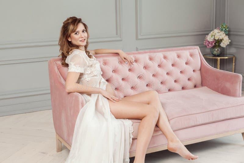 Schwangere junge Frau im weißen Kleid-peignoir, das auf rosa Sofa, ihren nackten Bauch und schönen Beine zeigend sitzt und betrac stockbild