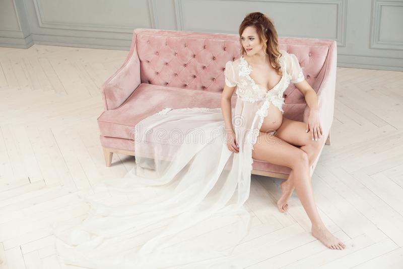 Schwangere junge Frau im weißen Kleid-peignoir, das auf rosa Sofa, ihren nackten Bauch und schönen Beine zeigend sitzt und weg sc stockbilder