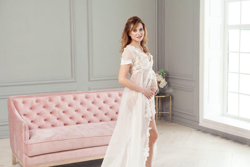 Schwangere junge Frau im weißen Kleid-peignoir, das nahe dem rosa Sofa, mit Liebe ihren Bauch halten steht lizenzfreie stockfotografie