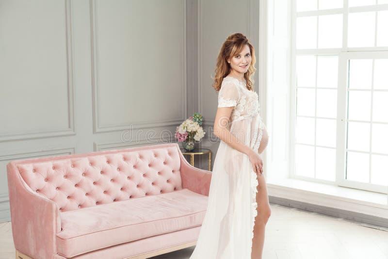 Schwangere junge Frau im weißen Kleid-peignoir, das nahe dem rosa Sofa, mit Liebe ihren Bauch halten steht stockfoto