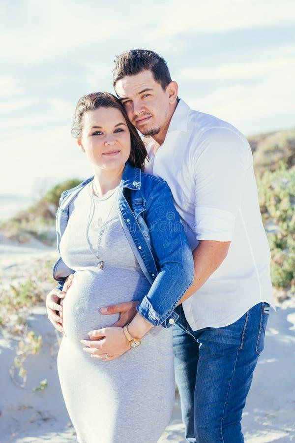 Schwangere junge Paare, welche die Kamera, stehend draußen betrachten lächelnd stockfotos