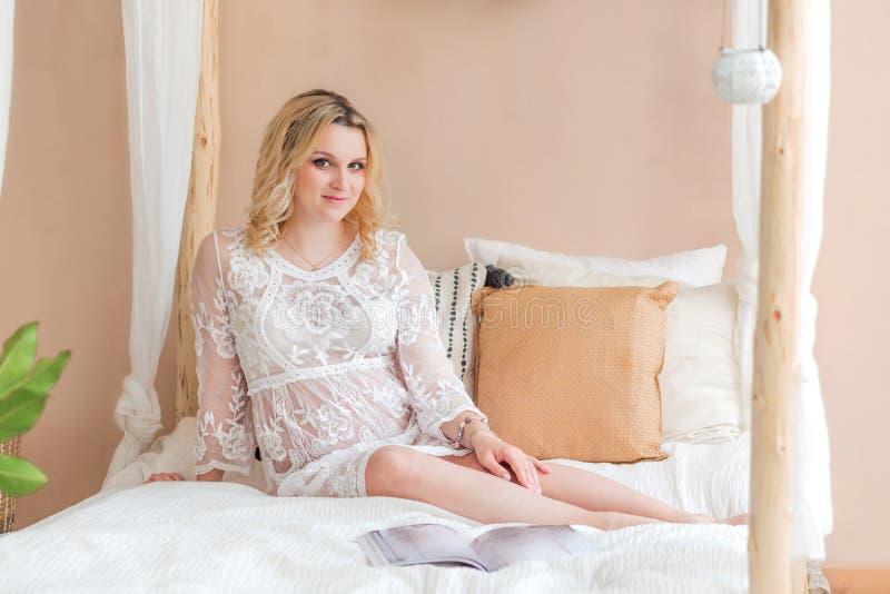 Schwangere Mädchenblondine im weißen Kleid, das auf dem Bett sitzt lizenzfreie stockfotografie