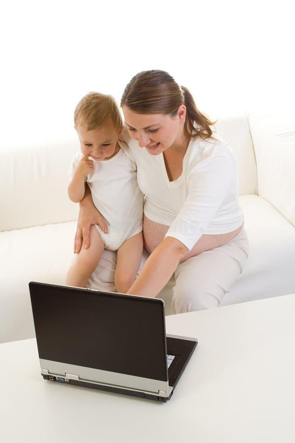 Schwangere Mutter, die Laptop verwendet stockbild