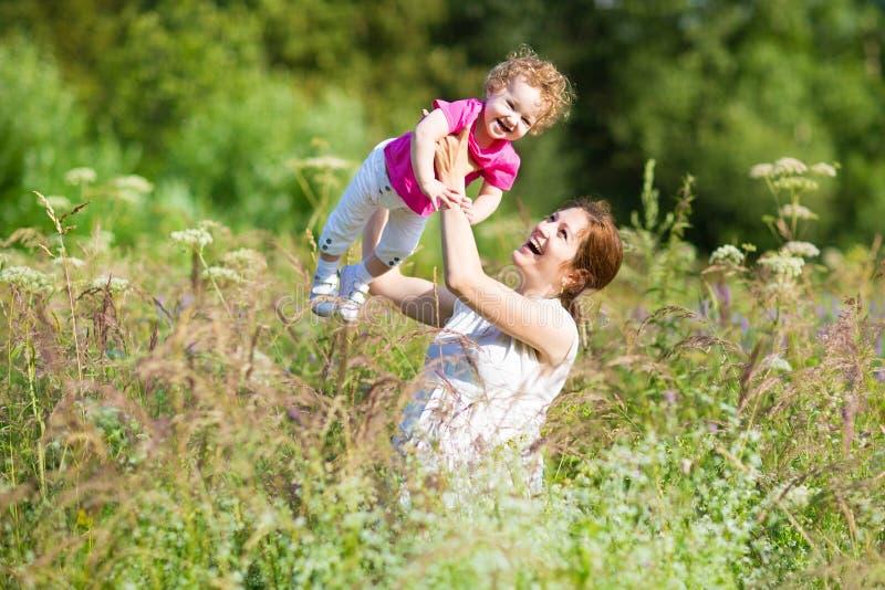 Schwangere Mutter, die mit ihrem Kleinkind in der Wiese spielt lizenzfreie stockfotos