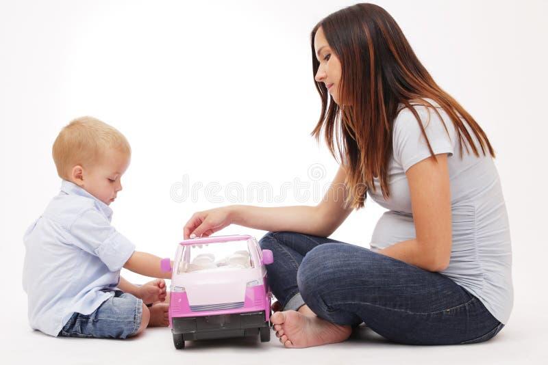 Schwangere Mutter, die mit ihrem Sohn spielt. lizenzfreie stockbilder