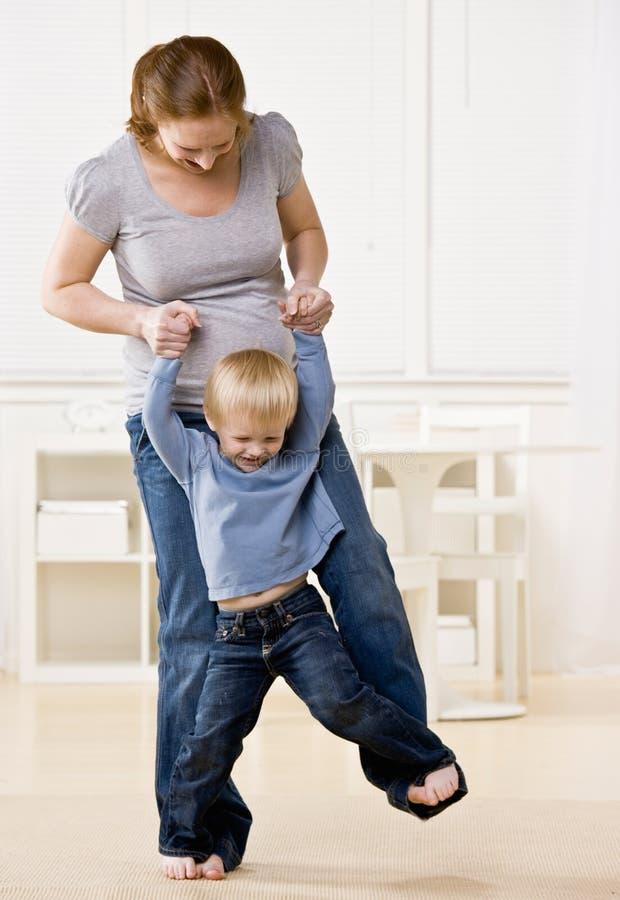 Schwangere Mutter tanzt mit ihrem Sohn auf ihren Füßen lizenzfreie stockfotografie