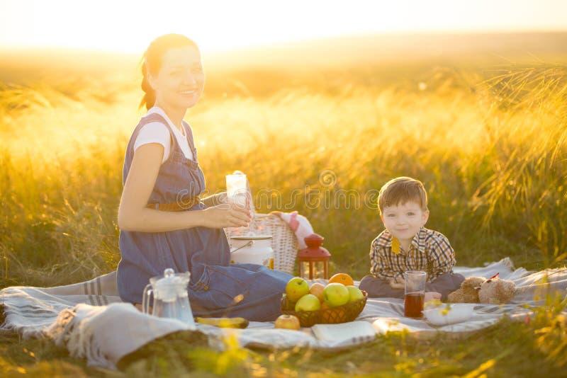 Schwangere Mutter und ihr netter kleiner Sohn draußen Glückliche Familie und Konzept der gesunden Ernährung lizenzfreie stockbilder