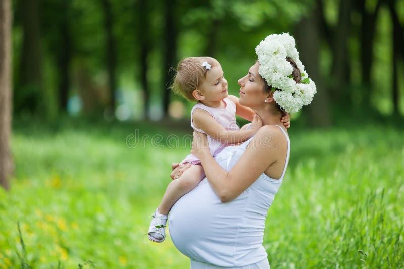 Schwangere Mutter und ihre Tochter lizenzfreies stockfoto