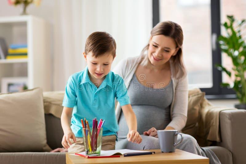 Schwangere Mutter und Sohn mit Arbeitsbuch zu Hause lizenzfreie stockbilder