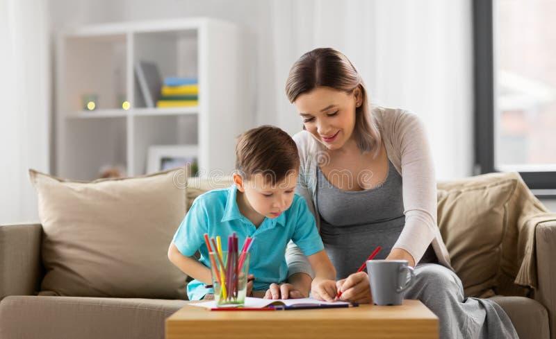Schwangere Mutter und Sohn mit Arbeitsbuch zu Hause stockfoto