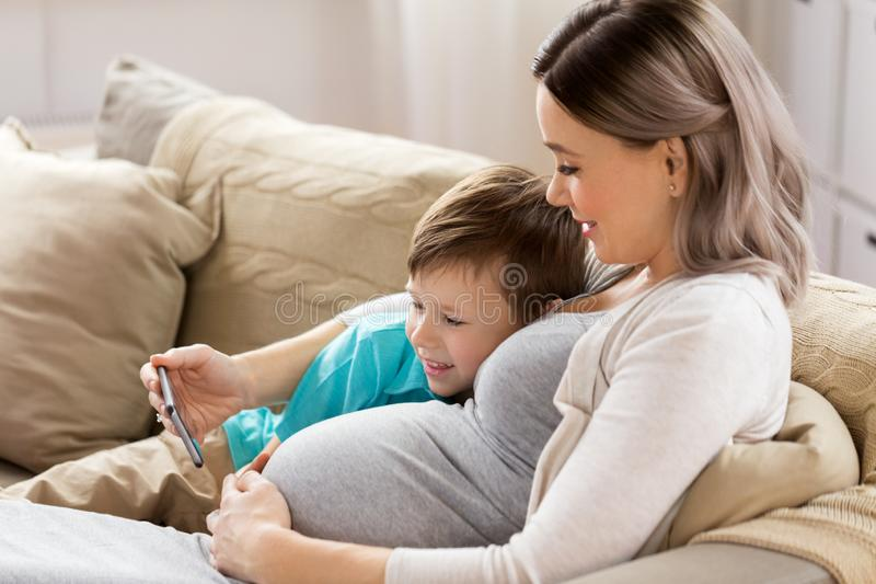 Schwangere Mutter und Sohn mit Smartphone zu Hause stockbild