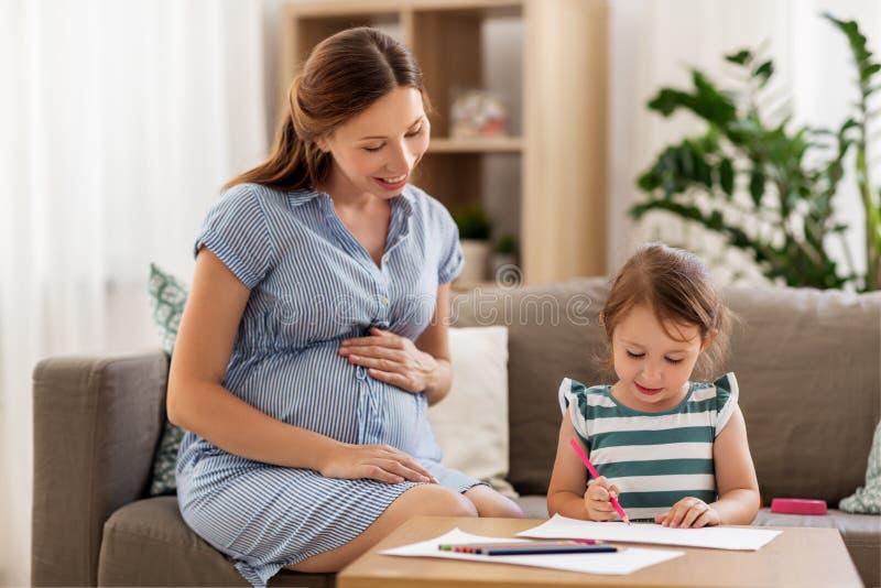 Schwangere Mutter und Tochter, die zu Hause zeichnet lizenzfreies stockfoto