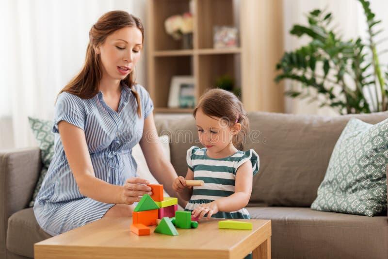 Schwangere Mutter und Tochter mit Bauklötzen lizenzfreie stockfotografie