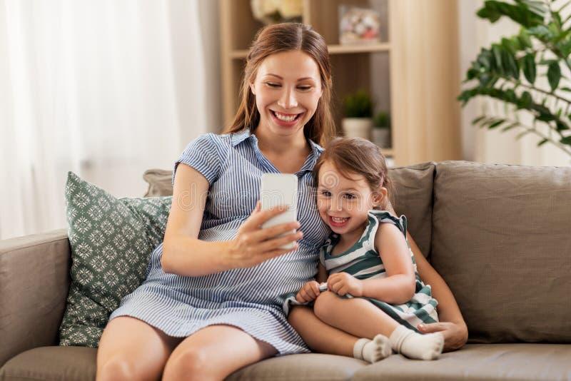 Schwangere Mutter und Tochter mit Smartphone stockbilder