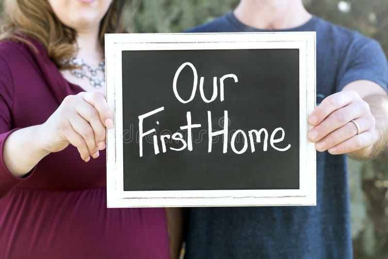 Schwangere neue Familie, die ihr neues Haus hält unser erstes Hauptzeichen kauft lizenzfreies stockfoto