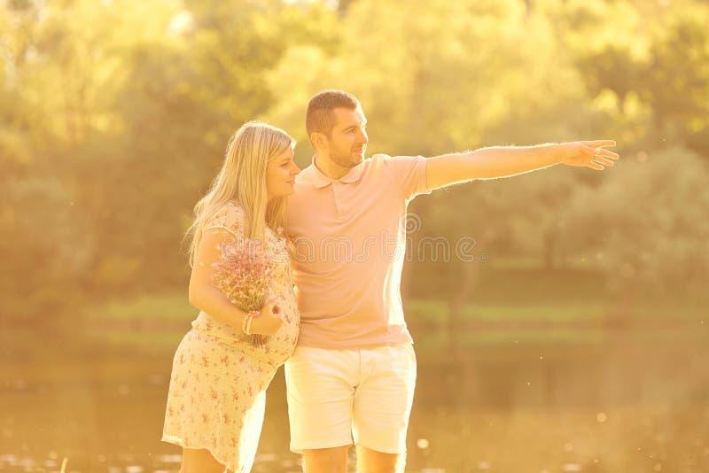 Schwangere Paare in den Strahlen des Sonnenlichts bei Sonnenuntergang Ehemannumarmungen stockfoto