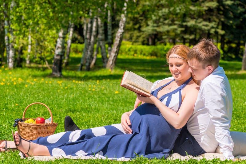 Schwangere Paare der Junge in einem Park, der ein Buch über Schwangerschaft liest lizenzfreies stockbild