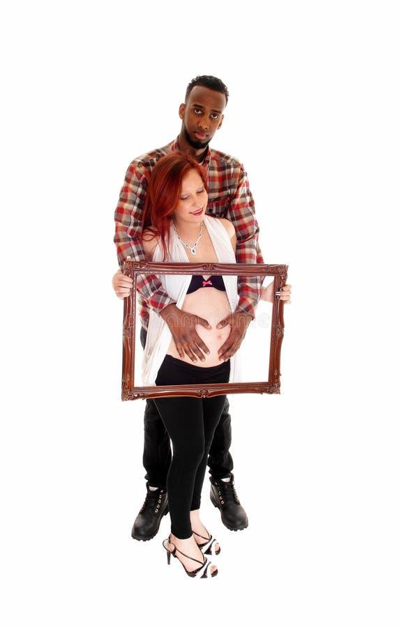 Schwangere Paare, die Bilderrahmen halten lizenzfreie stockfotos