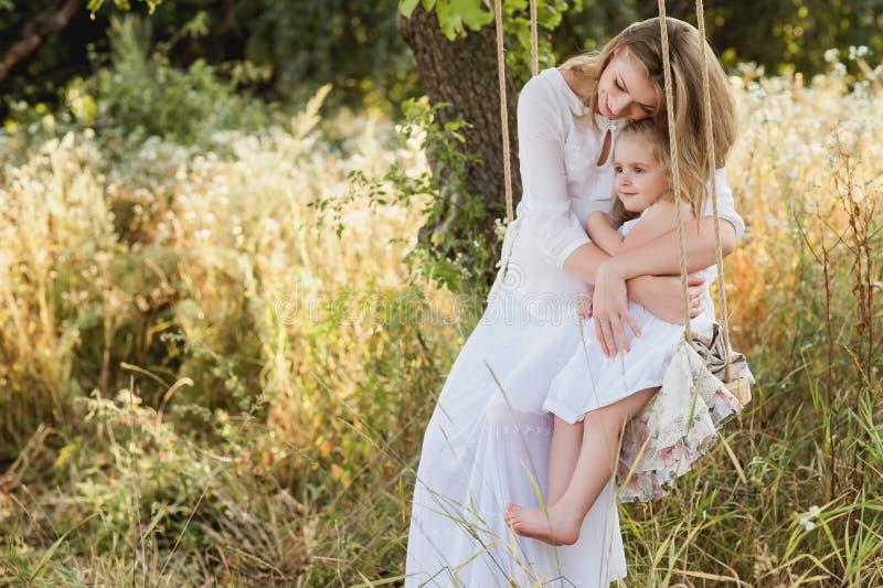 Schwangere schöne Mutter mit kleinem blondem Mädchen in einem weißen Kleid, das auf einem Schwingen, lachend, Kindheit, Entspannu lizenzfreies stockbild