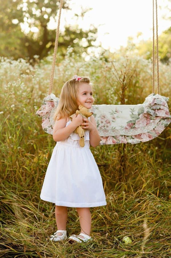 Schwangere schöne Mutter mit kleinem blondem Mädchen in einem weißen Kleid nahe einem Schwingen, lachend, Kindheit, Entspannung lizenzfreies stockfoto