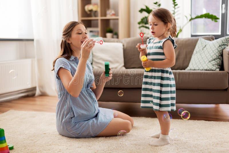 Schwangere Schlagseifenblasen der Mutter und der Tochter lizenzfreie stockfotos