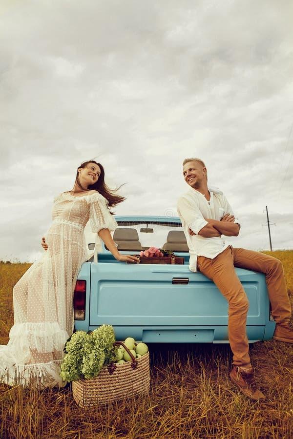 Schwangere und ihr Ehemann glücklich zusammen und schauen einander mit Liebe an Fotoaufnahme im Freien in der Nähe des Autos stockbilder
