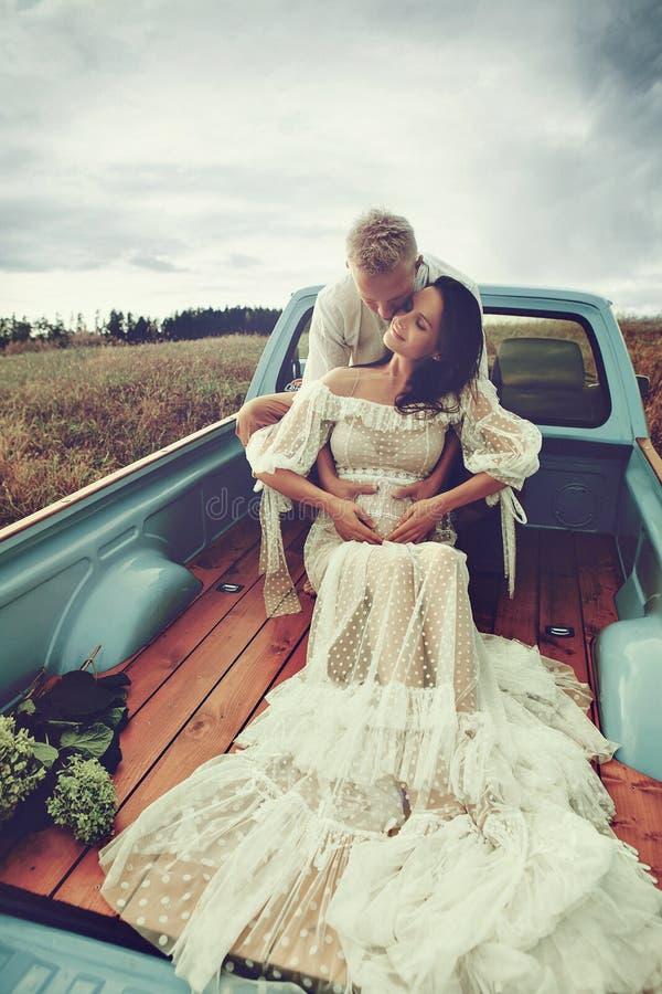 Schwangere und ihr Ehemann glücklich zusammen und schauen einander mit Liebe an Fotoaufnahme im Freien in der Nähe des Autos stockbild