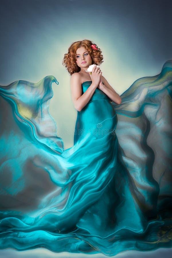Schwangere zarte Frau des schönen roten Haares im blauen Fliegenorganza-Gewebekleid mit Blume lizenzfreie stockbilder