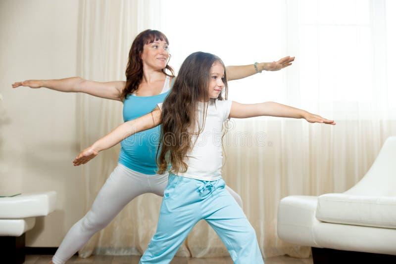 Schwangeres übendes Yoga des Mutter- und Kindermädchens zu Hause stockbild