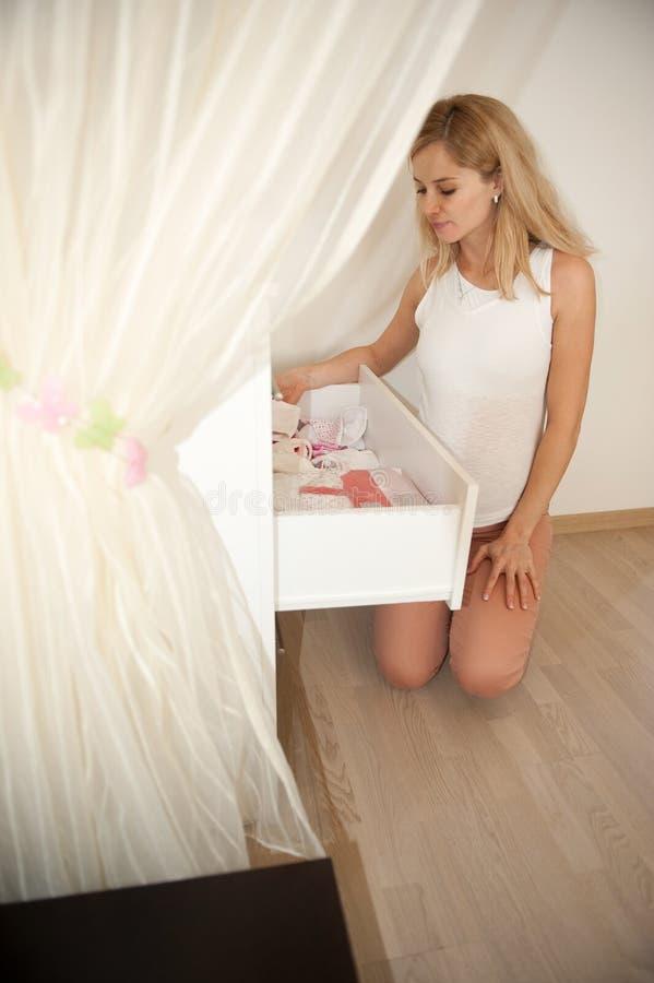 Schwangeres blondes nahes Kommode stockbild