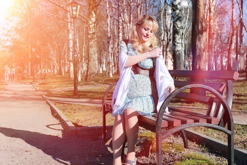 Schwangeres Mädchen auf einem Weg im Park Mädchen mit einem Bauch lizenzfreie stockbilder