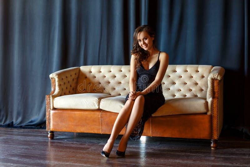 Schwangeres Mädchen, das auf der Couch in einem schönen Kleid sitzt stockfotografie