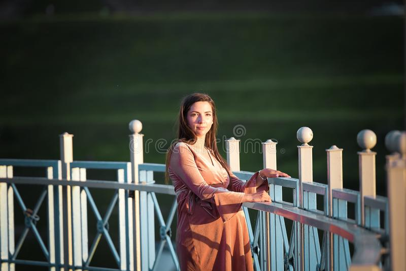 Schwangeres Mädchen, das entlang die Promenade geht Porträt eines Mädchens mit einem Magen Ein junges Mädchen in einem Sommerklei lizenzfreie stockfotos