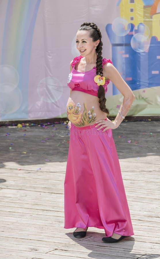 Schwangeres Mädchen, das ihren Bauch auf einem gemalten Karneval zeigt stockbild