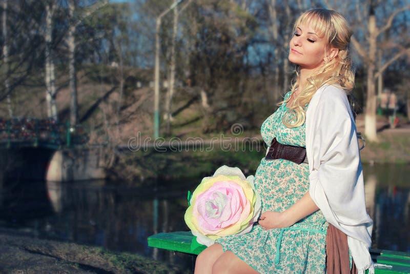 Schwangeres Mädchen, das um den Stadtpark im Vorfrühling geht stockfoto