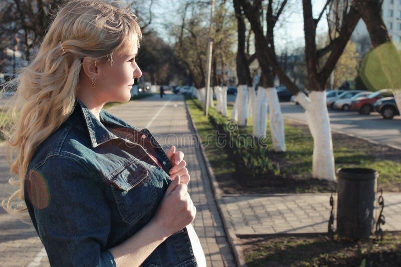 Schwangeres Mädchen, das um den Stadtpark im Vorfrühling geht lizenzfreies stockfoto