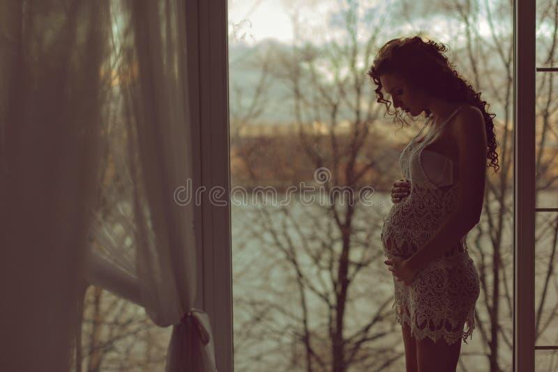 Schwangeres Mädchen mit dem gelockten Haar im Fischnetzkleid, das am w steht lizenzfreie stockfotos