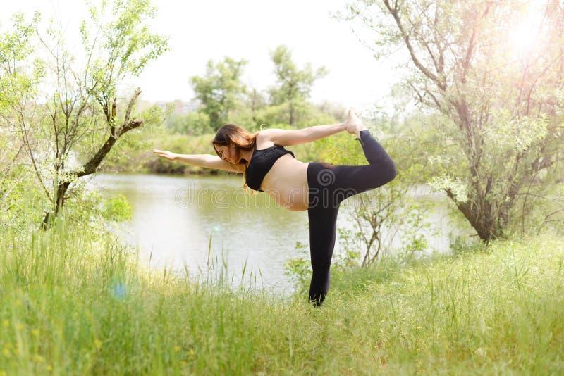 Schwangeres Schönheitsyogafreien auf dem Gras am sonnigen Sommertag stockfotos