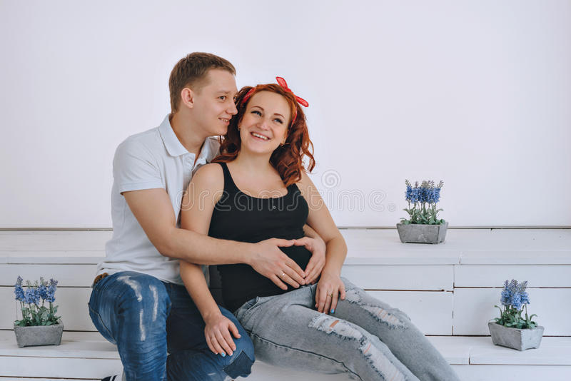 Schwangerschaft Der Bauch eines schwangeren Mädchens und ihres Ehemanns Der Ehemann hält seine Hand auf der Bauchfrau Zukünftige  lizenzfreie stockbilder